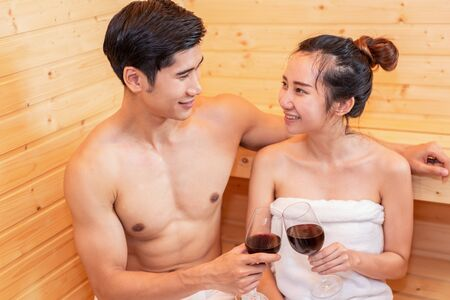 Asian couples toasting and drinking wine in sauna room for celebrating wedding anniversary. Healthy skin heat treatment with steam sauna concept. Holiday and Relax. Peopke lifestyles together