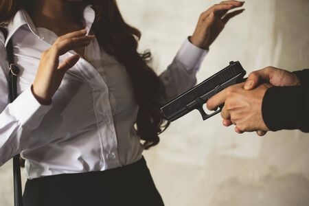 Robber force beauty woman to steal wallet or handbag by hand gun. Man gunpoint to victim. Fear of woman during facing and giving wallet to thieves. Criminal sexual and illegal violence crisis concept Stock Photo