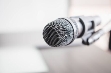 Closeup of microphone in lecture room background speech in seminar convention hall room. Mic speaker of teacher on podium in college or university. Workshop event and Entertainment broadcast concept. Фото со стока