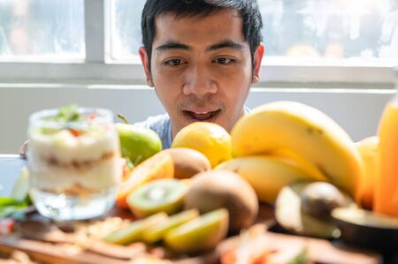 Asian man surprising when seeing many fruit yogurt with granola on table in kitchen background. Food and beverage ingredient concept. Happy vegetarian man hungry and ready to eat vegetable vitamin c
