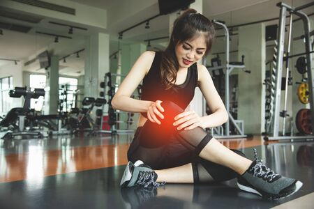 Asian woman injuries during workout at knee in fitness gym sport center. Medical and Healthcare concept. Exercise and Training theme. People healthy lifestyle and leisure activity problem Stock fotó