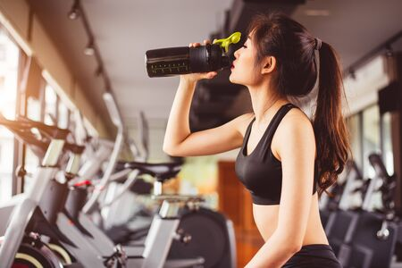 Asian beautiful woman drinking protein shake or drinking water in sport fitness training gym. Sports and people concept. Fitness and workout theme. Girl having activity on condominium or apartment 免版税图像