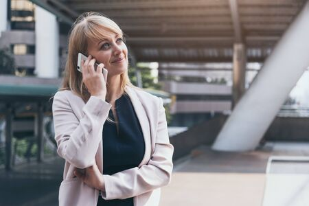 Happy businesswoman using smart phone to commnicate and talk to business agreement in urban city background. People lifestyles and technology concept. Outdoor working and social distancing concept