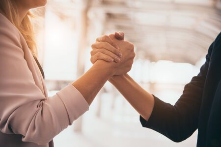 Business partnership meeting trust handshaking concept. Businesswomen doing arm wrestling. Successful business people contract promise for good confidence dealing with skyscraper building background 免版税图像