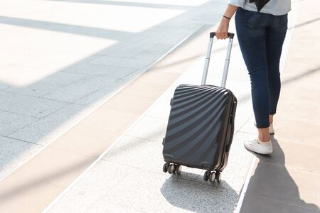 Close up woman and suitcase trolley luggage in airport. People and lifestyles concept. Travel and Business trip theme. Woman wear jeans going on tour and traveling around the world by alone solo girl