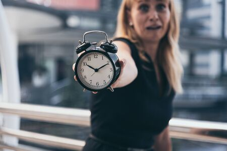 Business women show alarm clock and shocked with late in rush hours when going to work in city urban background. Deadline and wake up late. People lifestyle and daily life planner concept.