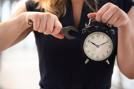 Business woman try to adjust time  on alarm clock after shocked with late in rush hours when going to work in city urban background. Deadline and wake up late. People lifestyle daily life concept.