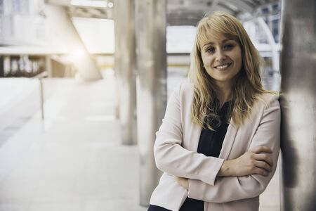 Happy beautiful smiling business woman at outside of office background. CEO manager businesswoman in formal wear suit having confidence and cheerful. People lifestyle concept. Looking at camera