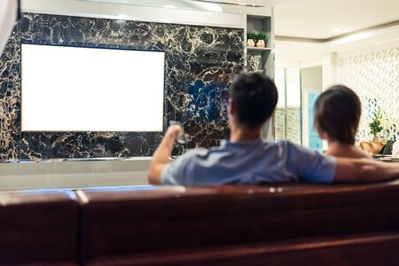 Asian couples watching white blank screen display television for advertising template background.  People lifestyles concept. Lockdown social distancing work from home. Selective focus on TV