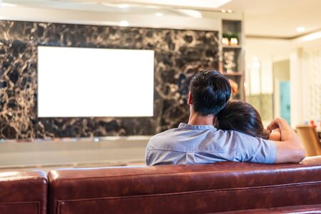 Asian couples watching white blank screen display television for advertising template background.  People lifestyles concept. Lockdown social distancing work from home. Selective focus on couples