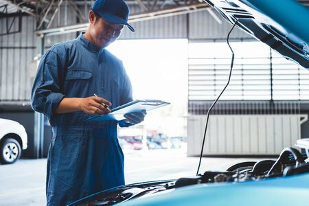 Car mechanic holding clipboard and checking to maintenance vehicle by customer claim order in auto repair shop garage. Engine repair service. People occupation and business job. Automobile technician