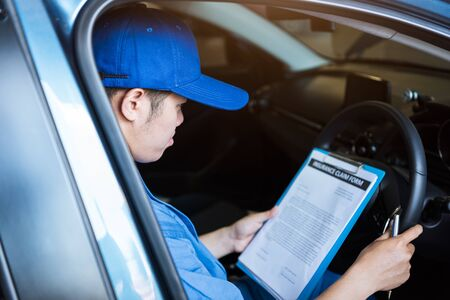 Mechanic holding clipboard and checking inside car to maintenance vehicle by customer claim order in auto repair shop garage. Repair service. People occupation and business job. Automobile technician