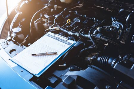 Clipboard on car with car insurance claim form for customer maintenance vehicle checklist in auto repair shop garage. Engine repair service concept. Business technical mechanics support for fixing car