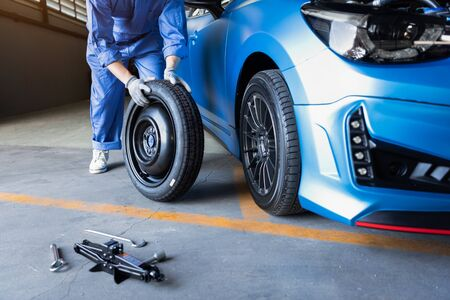 Car mechanics changing tire at auto repair shop garage. Transportation and Business working people concept. Automobile technician maintenance vehicle by customer claim order. Wheel repair service