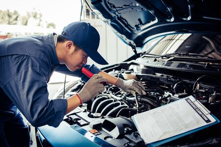 Car mechanic technician holding flashlight checking engine with checklist clipboard to maintenance vehicle by customer claim order in auto repair shop garage repair service. People occupation business