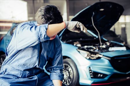 Car mechanic resting from exhaustion and wiping sweat from tired hard work in auto repair shop garage. Business industry and transportation concept. People occupation and job. Automobile technician