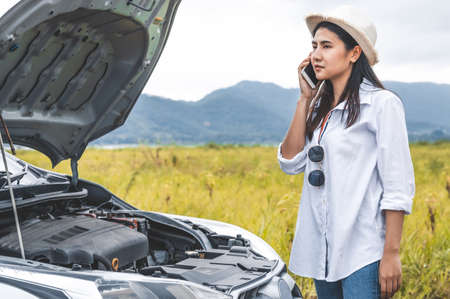 Asian woman calling car mechanic service for repairing breakdown broken car by mobile phone during driving to destination. Car maintenance and transportation concept. People travel and landscape theme