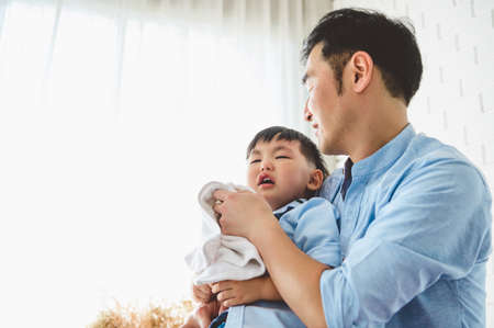 Asian Japanese father consoling his crying son and wiping tears in bedroom at his home white curtain background. People lifestyle health. Medical and Health concept. Negative emotion theme.