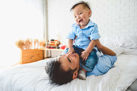 Two Asian father and his son are lying and playing in bed at bedroom. Child on top of Japanese dad body happily. Leisure time. People lifestyle health affection love.