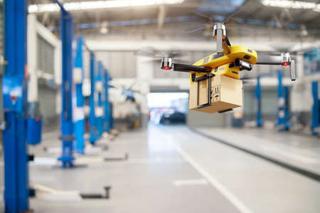 Flying delivery drone transferring parcel box from distribution warehouse to automotive garage customer service repair center background. Modern innovative technology and gadget concept. 免版税图像