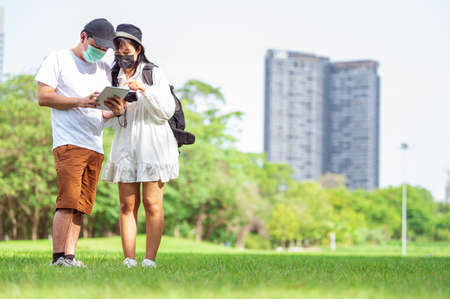 Asian couples with facial mask searching for tourist information through tablets of amazing places to visit in urban with building and park background. Technlogy and Travel concept. New normal theme 免版税图像