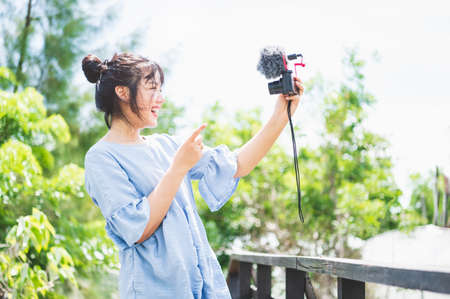 Asian woman in blue dress in public park carrying digital mirrorless camera and taking photo without facial mask in happy mood. People lifestyle and leisure concept. Outdoor travel and Nature theme. 免版税图像
