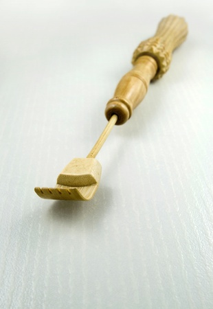 Close up perspective of a bamboo back scratcher shaped like a hand. photo