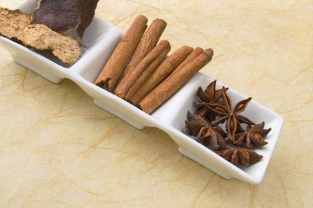 tangerine peel: Star anise, cinnamon sticks and tangerine peel - herbs and spices in white ceramic dish. Stock Photo