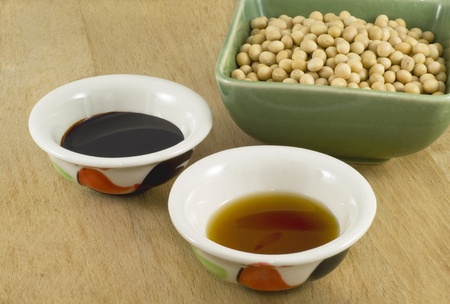 source: Thick and light soy sauce in ceramic dish and soy beans in green porcelain bowl. Stock Photo