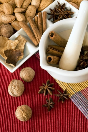 holistic health: Walnuts, almonds and spices ingredients on kitchen table with white mortar and pestle. Stock Photo