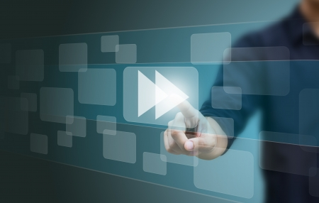 fast forward: hand pushing a fast forward button on a touch screen interface