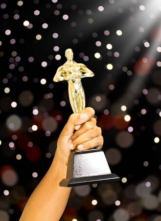 Close up of hand and gold trophy Stock Photo - 14589300