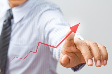 estadisticas: Empresario dibujar una flecha en aumento, lo que representa el crecimiento del negocio