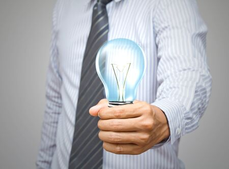 save electricity: Light bulb in hand
