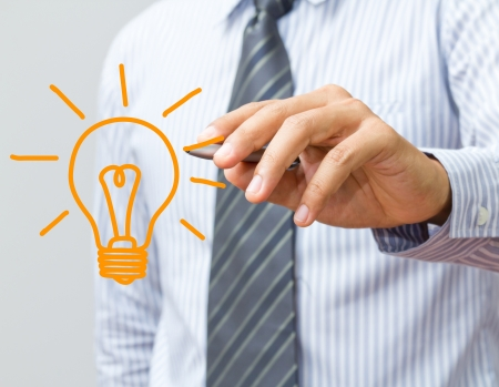 new idea: hand with a pen drawing light bulb Stock Photo