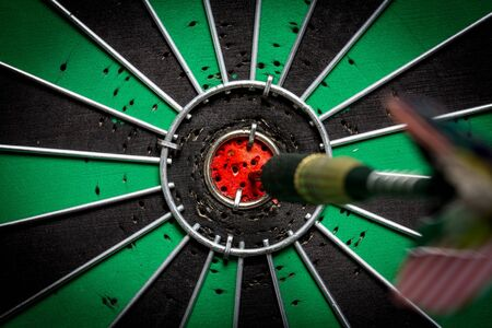 bull s eye: Dart in bulls eye of dartboard with shallow depth of field concept for hitting target