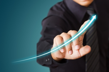 Empresario tocar una flecha ascendente, lo que representa el crecimiento del negocio