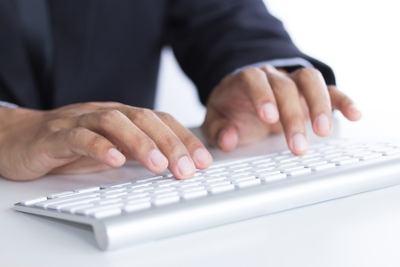 man s hands typing on keyboard  Selective focus photo