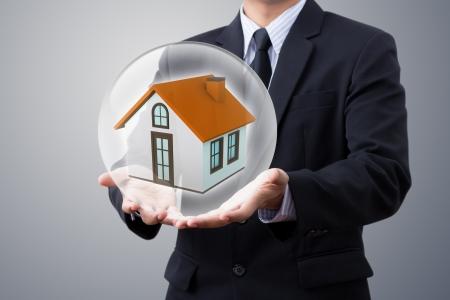 bola de cristal: ahorro de las manos peque�a casa en la bola de cristal Foto de archivo
