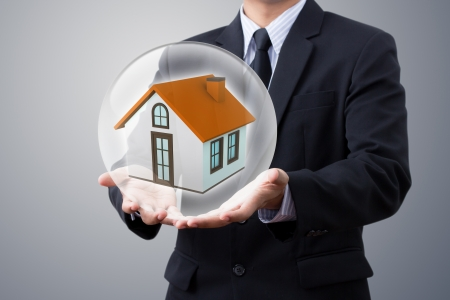 protecting: hands saving small house in crystal ball