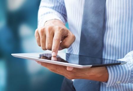 Business hand presses on screen digital tablet