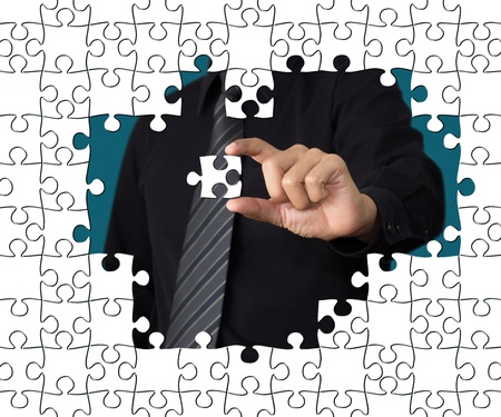 Business concept: Hand holding one pieces of a puzzle photo