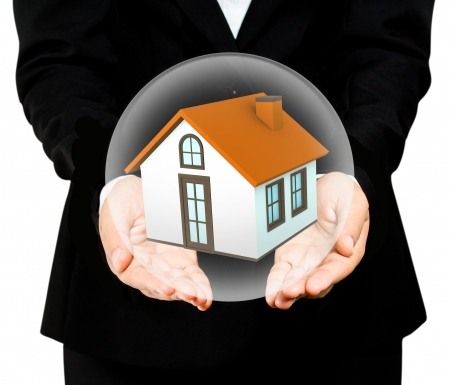 hands saving small house in glass ball Stock Photo
