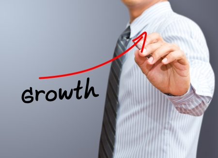 Businessman drawing a rising arrow, representing business growth  photo