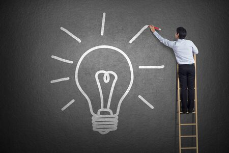 ladder of success: businessman standing on a ladder drawing light bulb Stock Photo