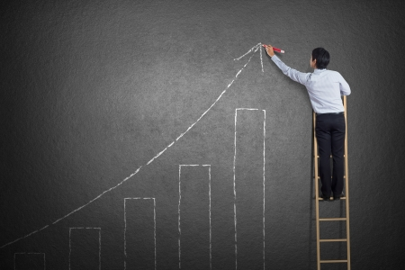 business man standing on ladder drawing growth chart on wall 스톡 콘텐츠