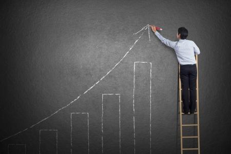 subiendo escaleras: Hombre de negocios de pie en la escalera curva de crecimiento de dibujo en la pared