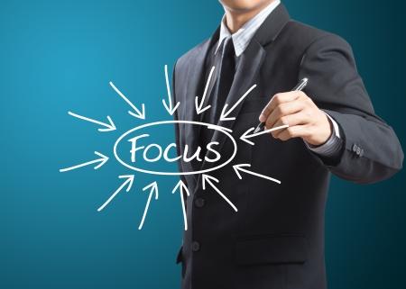 business man writing target on focus