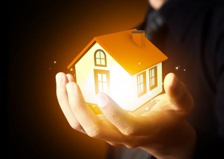 household insurance: Businessman holding home model