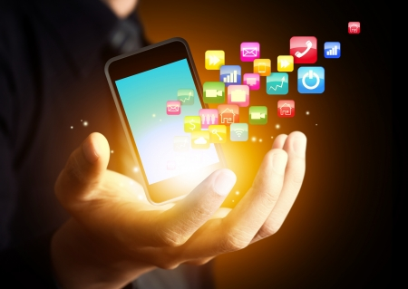smartphone hand: Smart phone with cloud of application icons in consumer hand Stock Photo